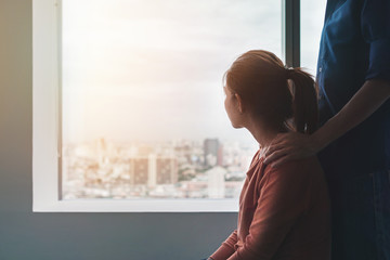 Psychologist sitting and touch young depressed asian woman for encouragement near window with low light environment, PTSD Mental health concept, Selective focus.