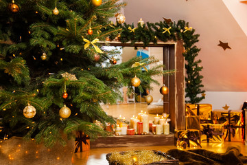 Christmas decorations in the studio, big natural fir tree with golden balls, bows and snowflakes, wooden fireplace and candles on it and brown cozy armchair