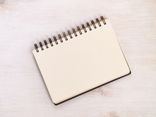 Spiral notebook with dotted pattern on white wooden table. Top view.