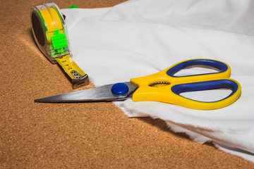 scissor and Tape measure meter over a white cloth