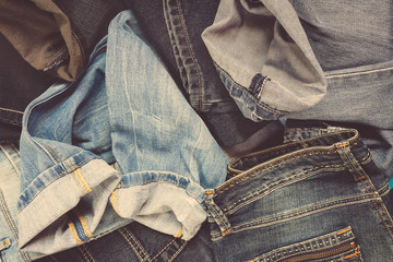 top view Pile of blue jeans, jeans background. Set of old jeans in vintage style toned. Denim