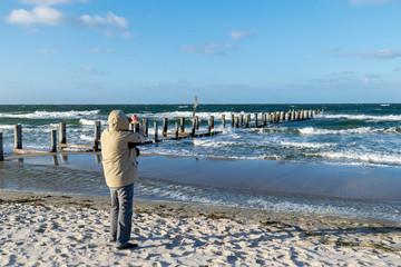 Mann fotografiert die Ostsee am Strand