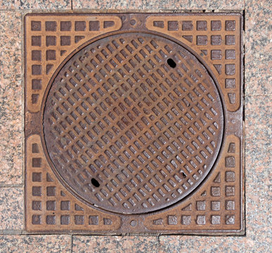 Old rusty sewer hatch on an old metal plate. View from above.