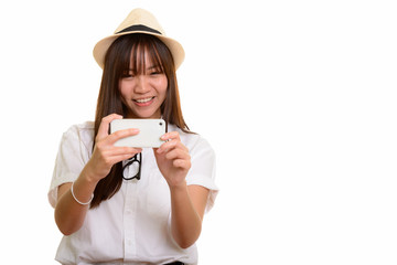 Young happy Asian teenage girl smiling and taking picture with m