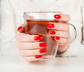 female hands holding a transparent cup of hot tea