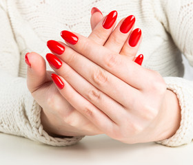 young woman with red manicure on nails