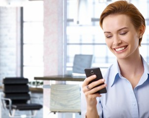 Young businesswoman using mobilephone at office