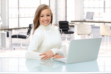 Woman working with laptop at office desk