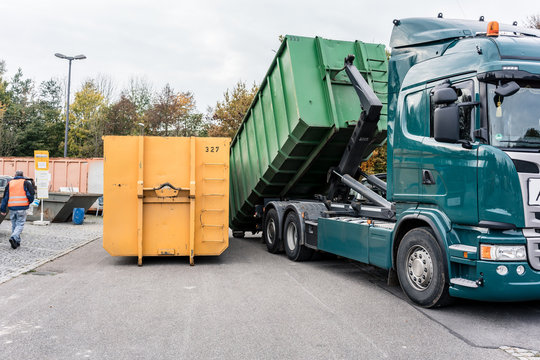 Truck loading container with waste in recycling center to transport