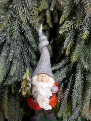 Christmas garden gnome in the fir forest with a small christmas tree in hand