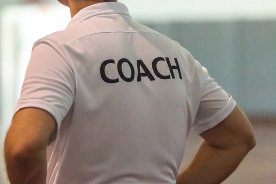 Back view of male sport coach with word COACH written on back of his shirt