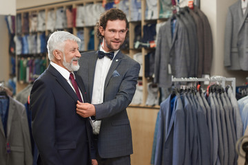Attractive helping customer trying on jacket in show room.