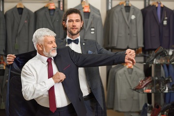Atractive guy and older grey man in costumes in male store.