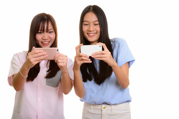 Two young happy Asian teenage girls smiling and taking picture w