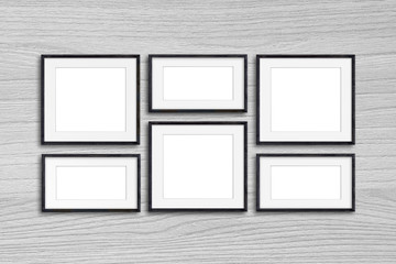 Black photo frames mock up on wooden panels wall