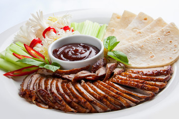 Duck in Beijing with cucumbers and pancakes. Sliced in pieces