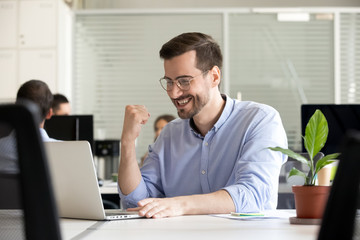Excited motivated male worker happy by receiving good news in email looking at laptop, lucky business man winning online, getting promotion, celebrating success profit, satisfied with great result