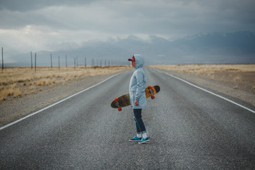 Young sporty girl with longboard is standing on a deserted road