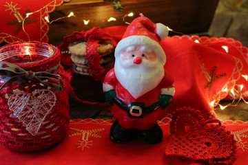 Porcelain retro Santa Claus, chocolade cookies on the red homemade Christmas tablecloth