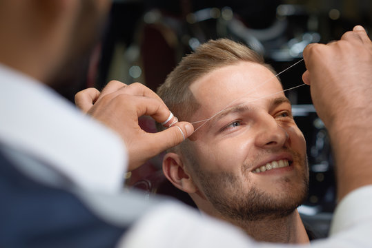 Closeup of process of threading procedure in barber shop