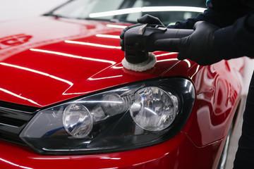 Obraz Car detailing - Man with orbital polisher in repair shop polishing car. Selective focus. - fototapety do salonu