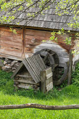 View on old wooden ancient water mill in open-air museum, spring time.