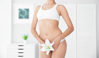 Young woman with flower showing smooth skin after bikini epilation indoors