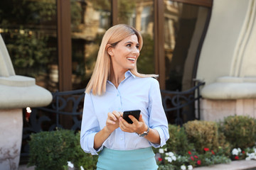 Female real estate agent with smartphone outdoors