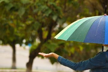 Woman with bright umbrella under rain on street, closeup