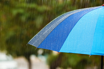 Bright umbrella under rain on street, closeup