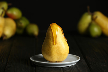 Pouring sweet syrup onto fresh ripe pear on table against blurred background