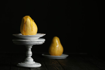 Pouring sweet syrup onto fresh ripe pear on table against dark background. Space for text