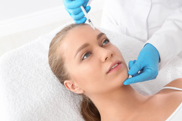 Young woman getting facial injection in clinic. Cosmetic surgery concept