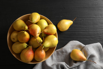 Flat lay composition with ripe pears on black wooden background