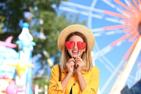 Beautiful woman with candies having fun at amusement park