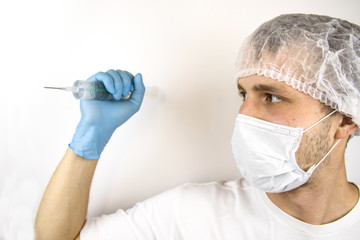 A young guy in a medical mask and hat is holding a medical syringe in front of him