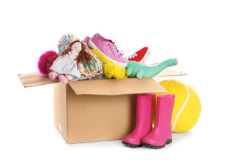 Donation box, shoes, clothes and toys on white background. Space for text