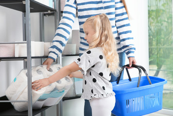 Young mother and little girl choosing toilet paper in shop