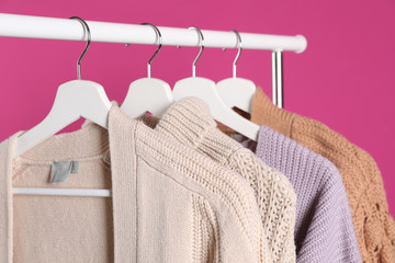 Fototapete - Collection of warm sweaters hanging on rack against color background, closeup