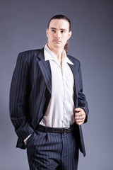 Young male confident male posing in gangster style suite. Studio isolated on gray background.