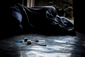 A man is a drug addict with a syringe using drugs lying on the floor. The concept of anti drugs. male drug addict, drug syringe.