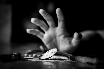 International Day against Drug Abuse. Young human hand trying to reach cooked heroin spoon on grungy concrete floor. Drugs addiction and withdrawal symptoms concept. Copy space.