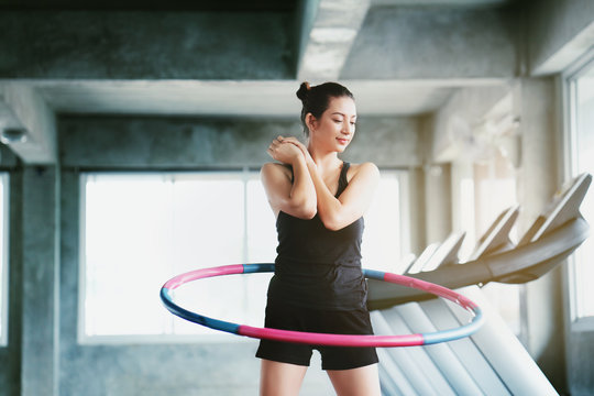 Beautiful Asian women wearing sportswear. Playing hula hoop in the morning gym. Helps to burn excess fat in body. Strengthens the muscles of the body. Increases blood flow to the brain. Good health
