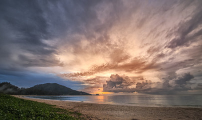 Amazing dramatic sky at sunset seen from a beautiful beach in Phuket, Thailand.