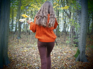 Teenage girl in autumn forest walking and holding yellow and orange leaves. Mysterious forest