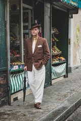 retro looking man on the street in front of a typical parisian store