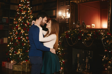 Fashionable and beautiful couple, sexy brunette model girl with bright makeup in a skirt and stylish handsome bearded men hugs and posing near the Christmas tree at interior decorated for New Year