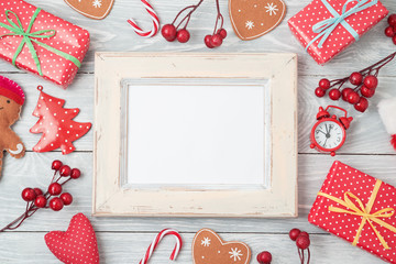 Christmas holiday background with gift boxes, photo frame and decorations on wooden table