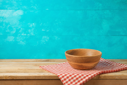 Empty wooden bowl on kitchen table with tablecloth over blue background