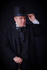 Actor in a black hat and a suit of the 19th century holding a cane